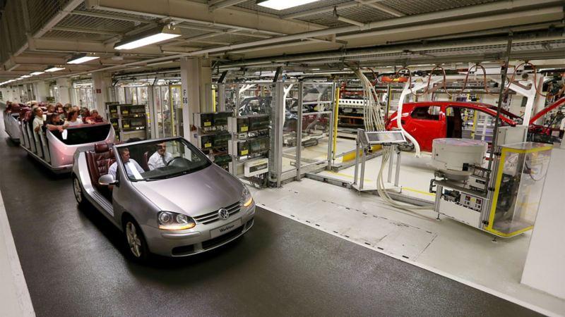 Eine offene Golfbahn fährt Besucher durch eine Produktionshalle