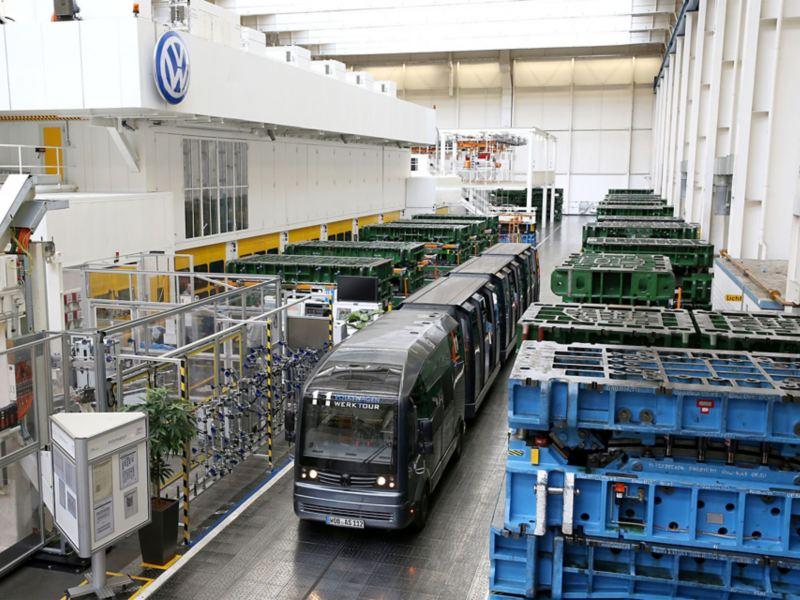 Eine Panoramabahn fährt durch eine Gasse in einer Werkshalle