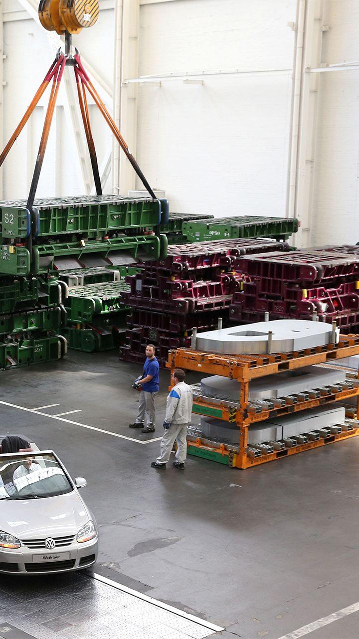 Eine offene Golfbahn mit zwei Waggons in einer Produktionshalle
