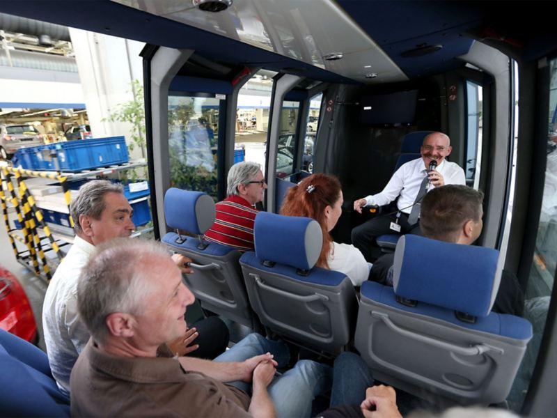 Im Inneren einer Panoramabahn spricht ein Tourbegleiter zu einer Besuchergruppe