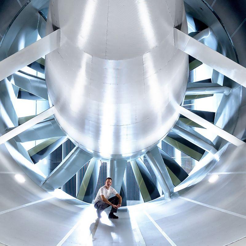Mann hockt in einem Windkanal des Volkswagen Entwicklungszentrums vor einer riesigen Turbine