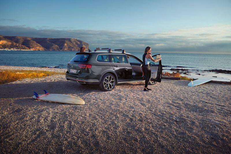 Passat Alltrack Heckansicht am Strand, Dachgepäckträger, Frau steht an geöffneter Beifahrertür, Surfbrett liegt im Vordergrund