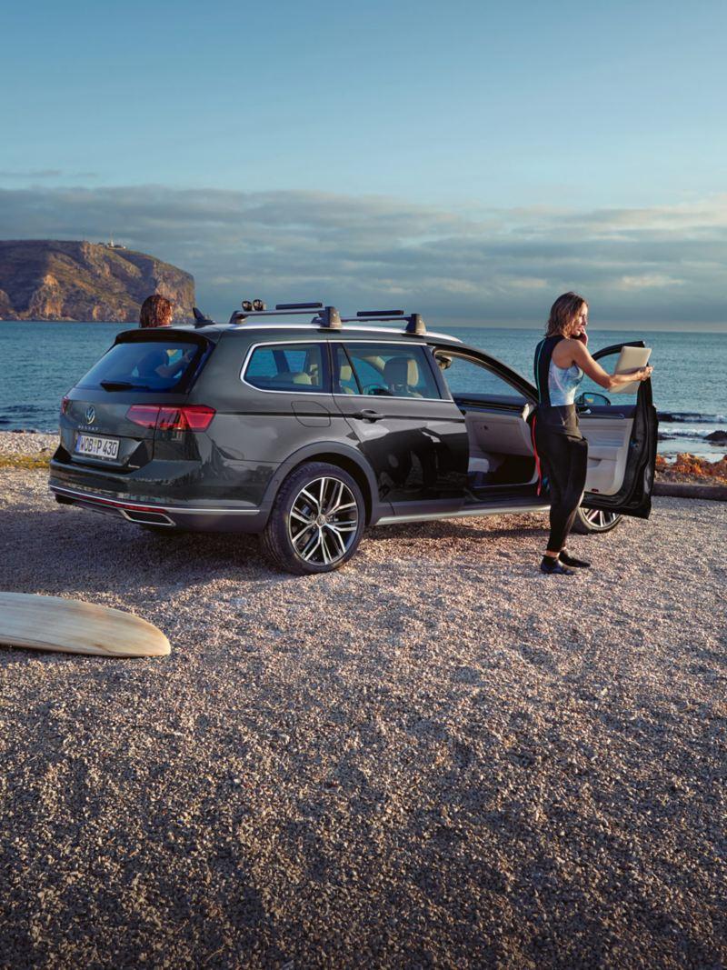 Passat Alltrack vista da dietro in spiaggia, portapacchi sul tetto, una donna è in piedi accanto alla porta del passeggero aperta, davanti c'è una tavola da surf