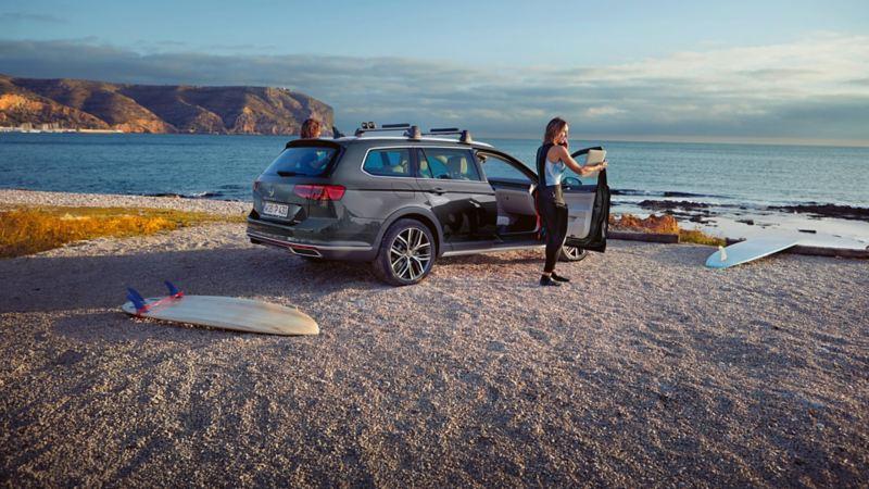Passat Alltrack achteraanzicht op het strand, imperiaal, een vrouw staat bij de geopende rechtervoordeur, surfplanken liggen op de voorgrond