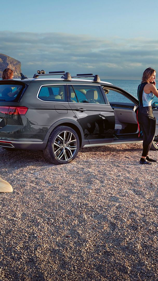 Passat Alltrack rear view on the beach, roof rack, woman standing at open passenger door, surfboard in the foreground