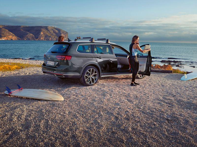 Passat Alltrack od tyłu na plaży, bagażnik dachowy, kobieta stoi przy otwartych prawych przednich drzwiach, na pierwszym planie deska surfingowa