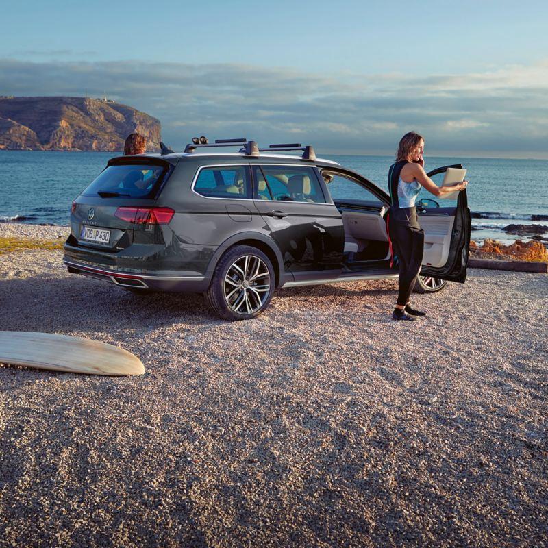 VW Passat Alltrack steht an Strand, im Hintergrund Meer und Klippen, Pärchen steigt aus, neben dem Fahrzeug liegen Surfbretter.