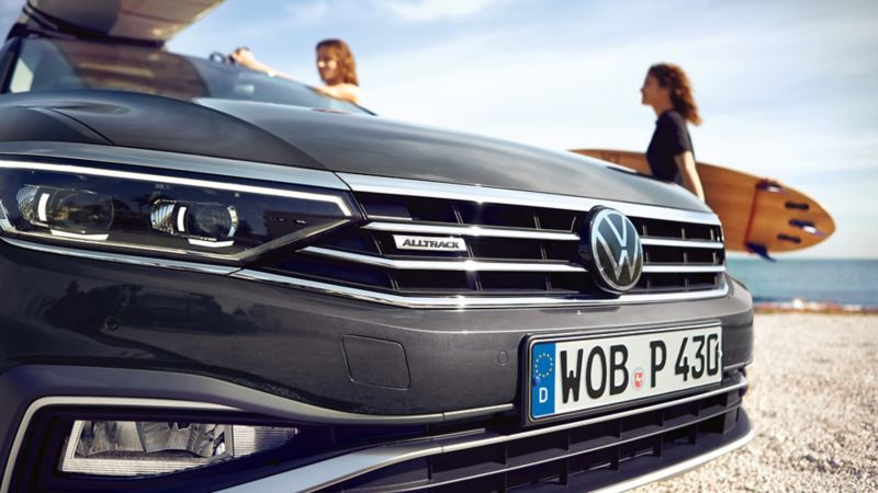 Passat Alltrack on the beach, diagonal close-up view of the front with Alltrack logo in the radiator grille, surfboard on the roof, two women in the background, one of them with surfboard under her arm