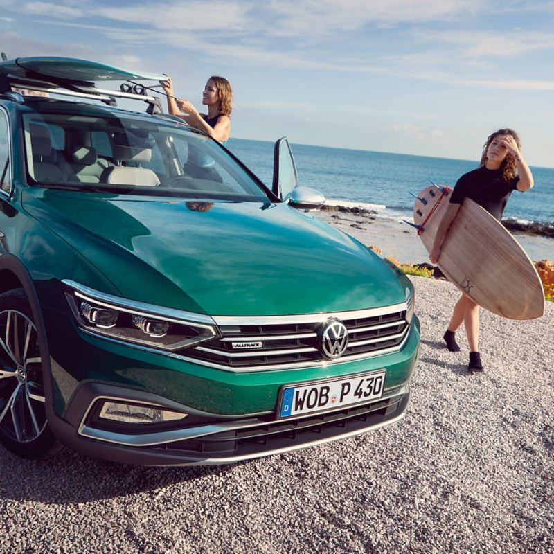 Mädchen am Strand neben einem Passat Alltrack