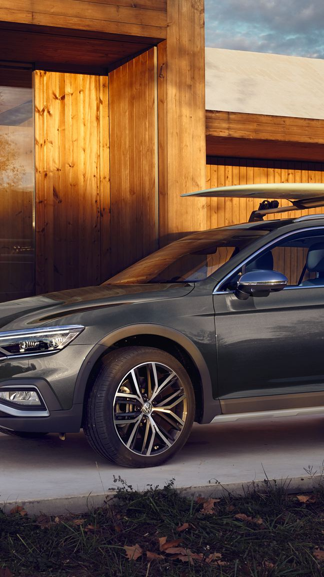 Volkswagen Passat Alltrack con una tavola da surf nel portabagagli sul tetto ferma davanti ad un coffee shop