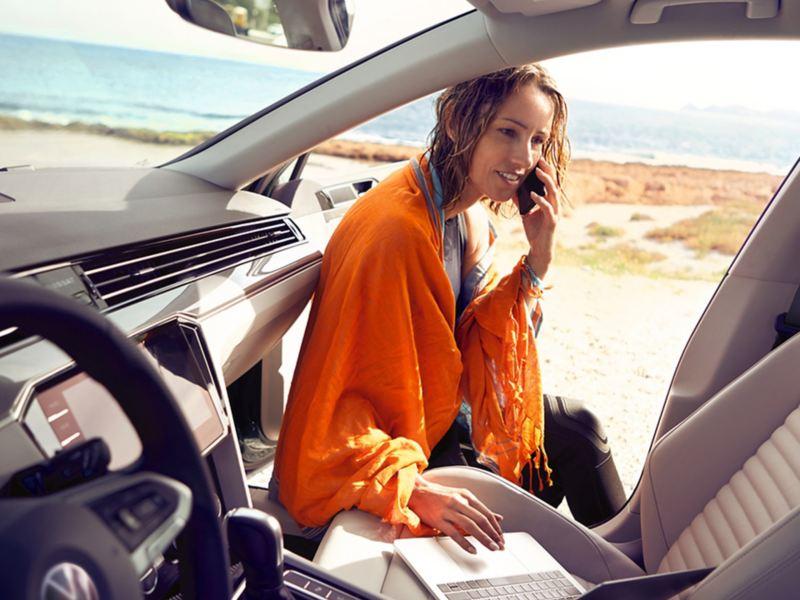 ragazza telefona e guarda laptop appoggiato sul sedile passeggero di Passat Alltrack Volkswagen