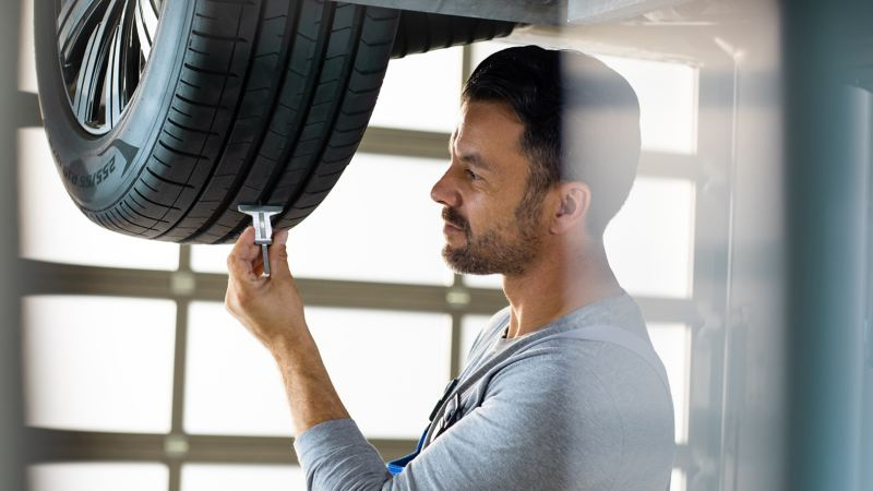 Ein Volkswagen Servicemitarbeiter misst die Reifenprofiltiefe eines VW Autos – HU/AU und Inspektion