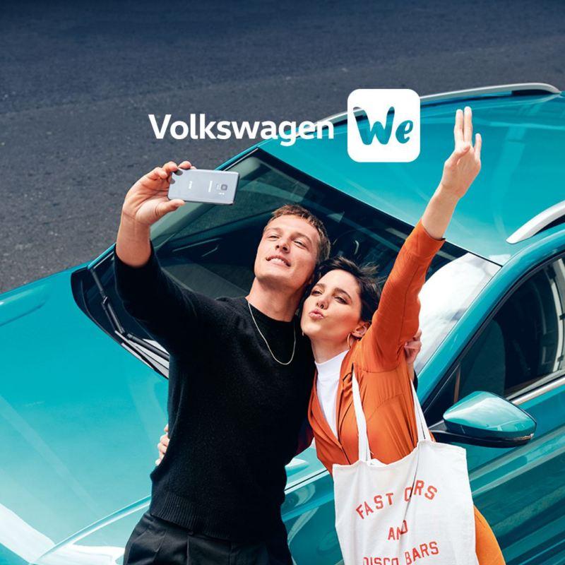 Ein Pärchen macht ein Selfie vor einem türkisenen VW T-Cross