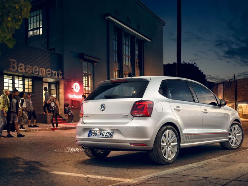 "A silver VW Polo 5 ""beats"" with grey and red design accents is parked on a road next to a club – Volkswagen older models"