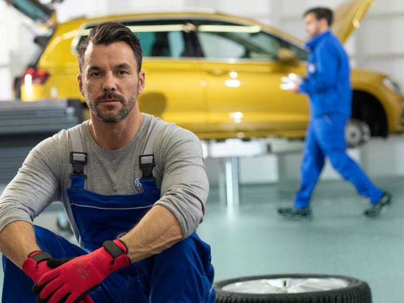Ein VW Servicemitarbeiter sitzt auf gestapelten Reifen in einer Werkstatt