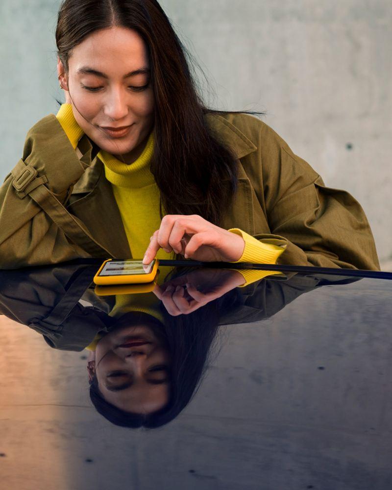 Eine junge Frau informiert sich online über aktuelle Aktionen – VW Angebote