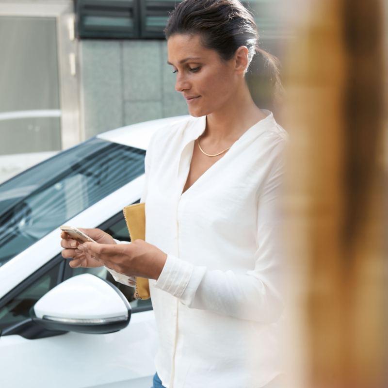 Eine Kundin  steht neben ihrem e-Golf und informiert sich online über aktuell verfübgare Elektroautos