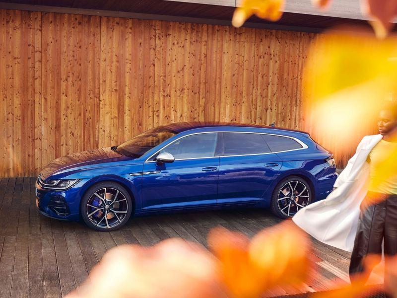 Ein VW Arteon R Shooting Brake in blau parkt vor einer Holzwand