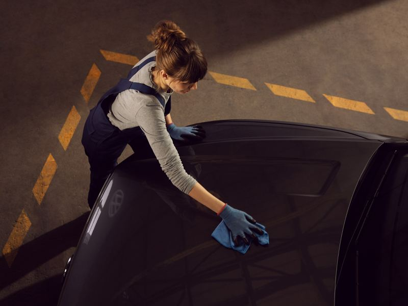Eine VW Servicemitarbeiterin reinigt das Exterieur eines VW Autos – Pflegeprodukte
