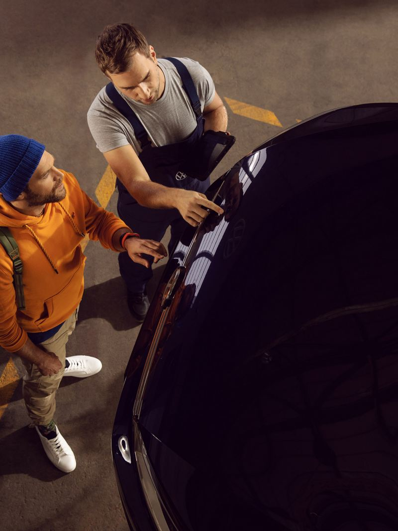 A VW service employee shows his customer the repaired vehicle body – Body and Paintwork Service