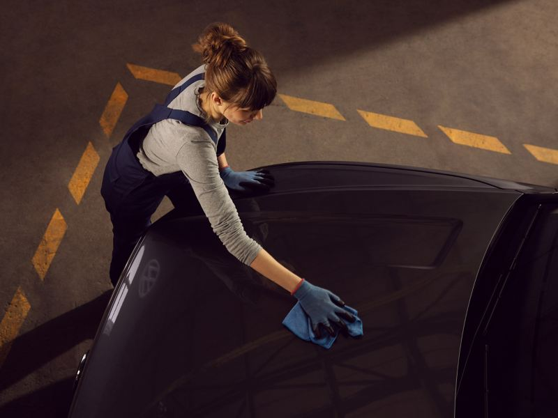 A VW service employee cleans the exterior of a VW car – care products