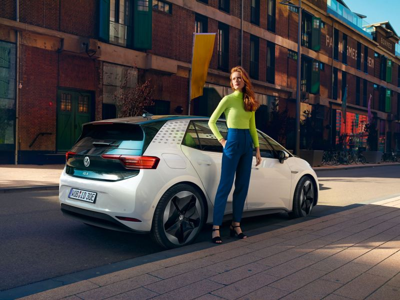 A woman stands at the roadside in front of her all-electric Volkswagen ID.3