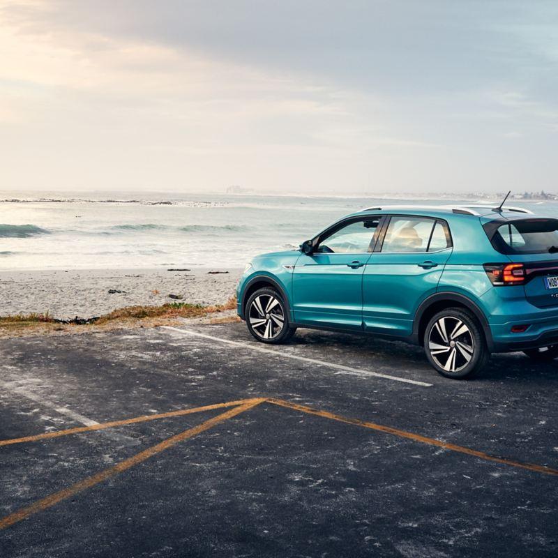 Ein türkiser VW T-Roc mit Ganzjahresreifen auf einem Parkplatz mit Blick auf das Meer