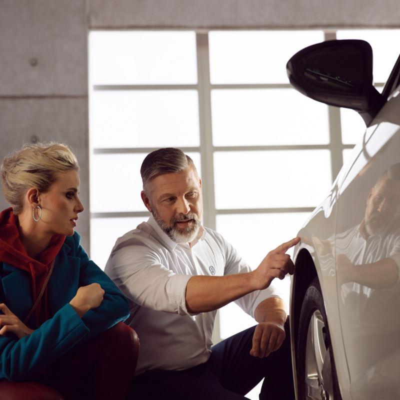 Ein VW Servicemitarbeiter zeigt einer Kundin neue Karosserieteile an ihrem Auto