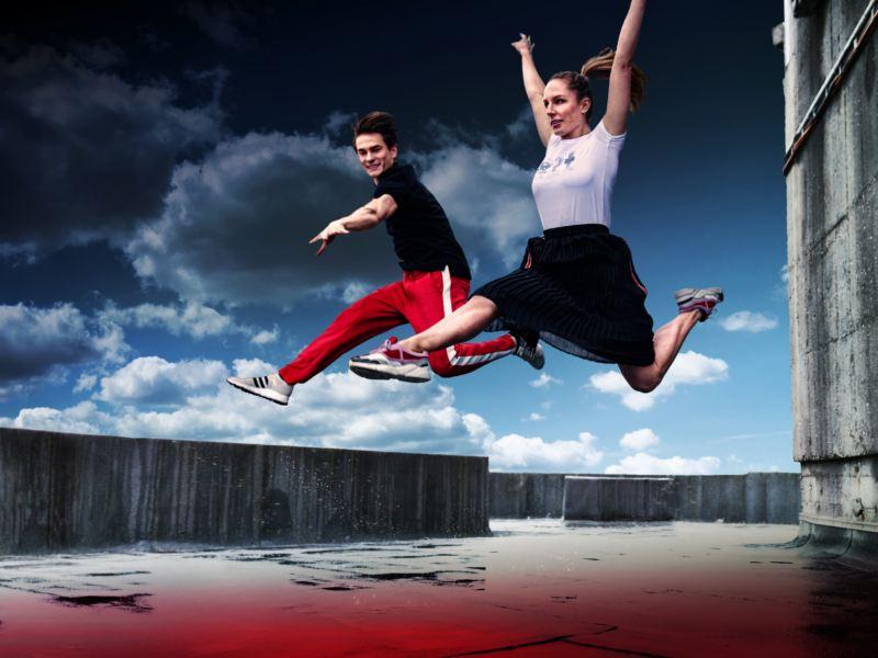 Ein Mann und eine Frau springen in die Luft – Volkswagen Lifestyle Kollektion