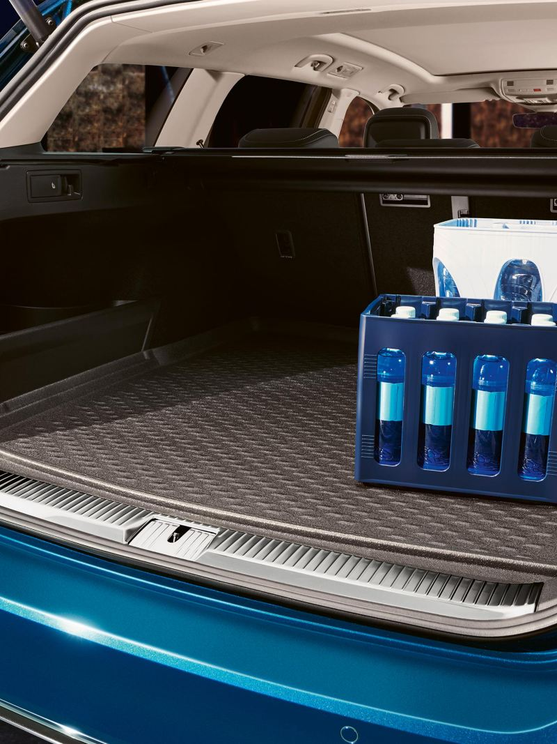 A blue VW car with open luggage compartment and water crates inside – Volkswagen luggage compartment solutions
