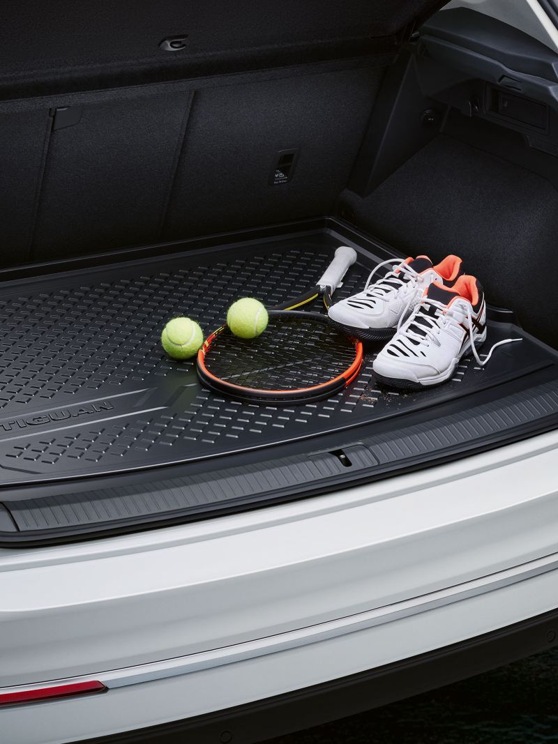 A white VW car with open luggage compartment and tennis equipment inside – Volkswagen Accessories luggage compartment solutions