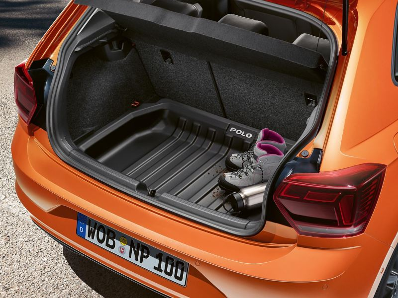 An orange VW Polo with open luggage compartment and sporting equipment inside – Volkswagen luggage compartment solutions
