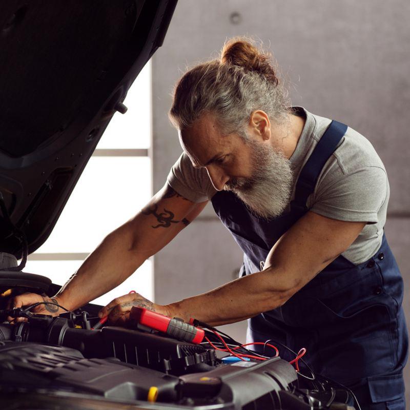 Ein VW Servicemitarbeiter prüft den Motor in einem VW Auto