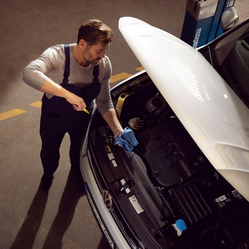 Ein VW Servicemitarbeiter prüft den Ölstand in einem VW Auto