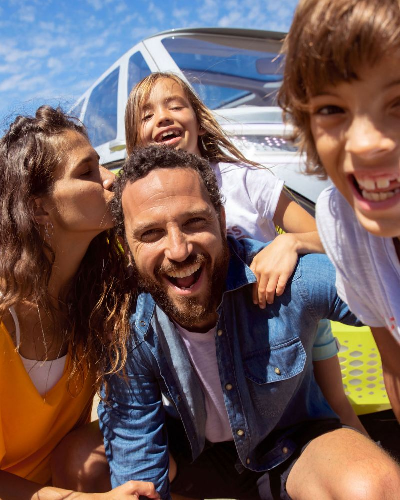 A boy takes a selfie of himself and his family in front of a VW ID.BUZZ – myVolkswagen