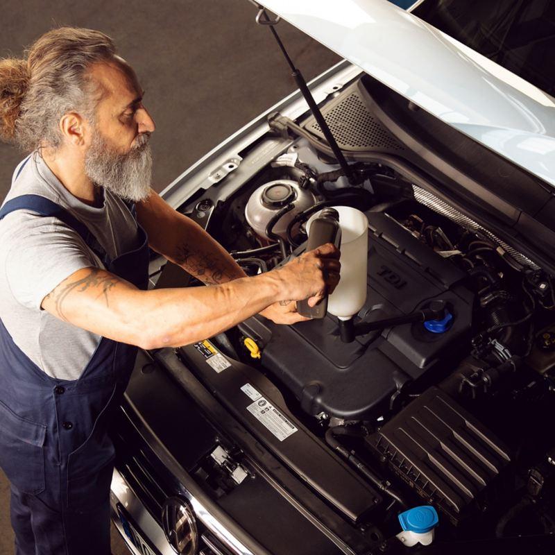 Ein VW Servicemitarbeiter kümmert sich um das richtige Öl für Ihr Auto