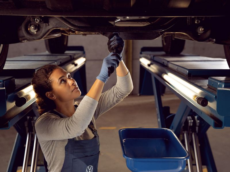 A VW employee changes the engine oil of a VW car –Volkswagen Oil Service