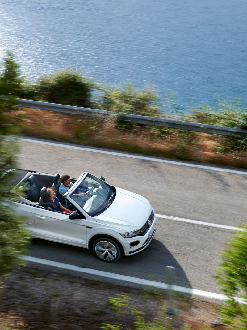 A white VW cabriolet is driving along the coast – carefree travel by car