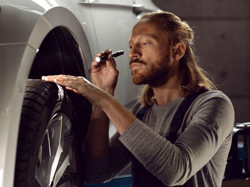 Ein VW Servicemitarbeiter prüft die Räder und Reifen von einem VW Auto