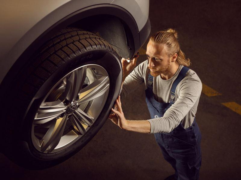 Ein VW Servicemitarbeiter kümmert sich um die Räder eines Volkswagen Autos – Räderwissen