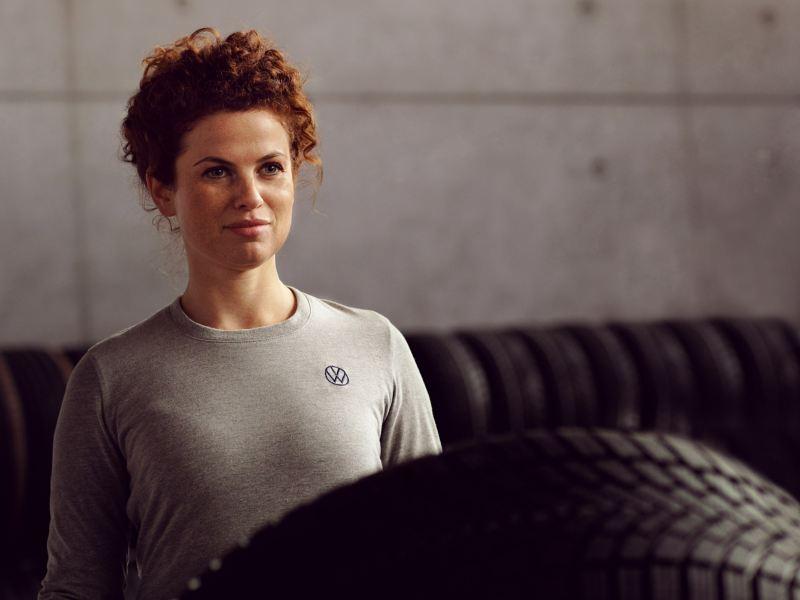 Eine VW Servicemitarbeiterin arbeitet mit Rädern – Reifenpakete