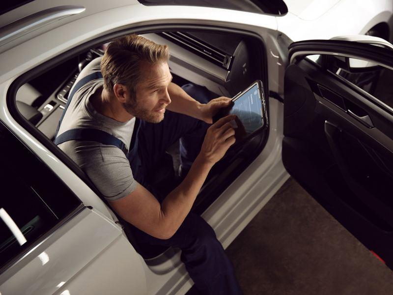 Ein VW Servicemitarbeiter prüft ein VW Auto – Reparaturen und Checks