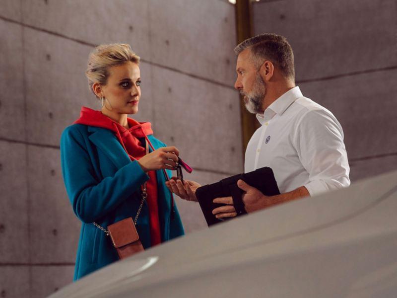 Una donna parla con un addetto VW Service.