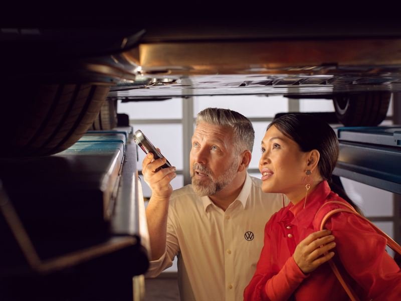 A VW service employee shows a customer something about her electric car – VW service for EV