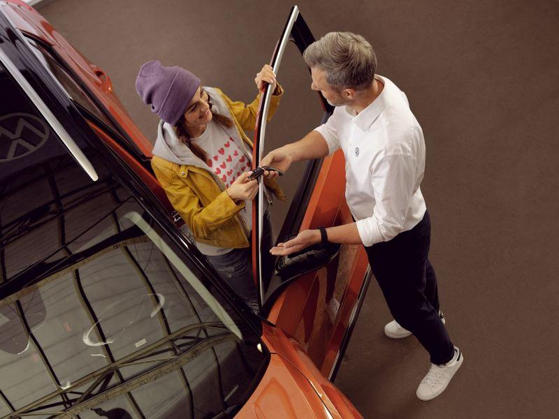 Ein VW Servicemitarbeiter überreicht seiner Kundin die Schlüssel für Ihren Volkswagen – VW Partner