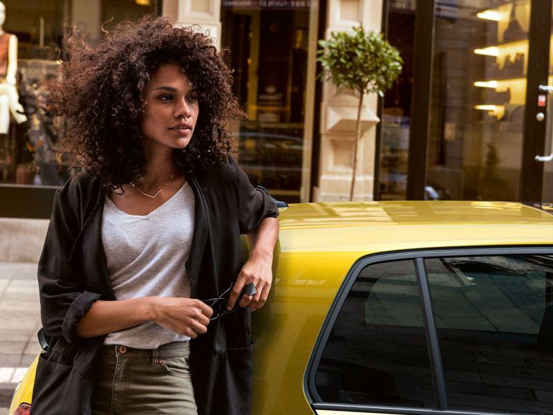 Eine Frau lehnt sich an ihr VW Auto – Volkswagen Vorgängermodelle