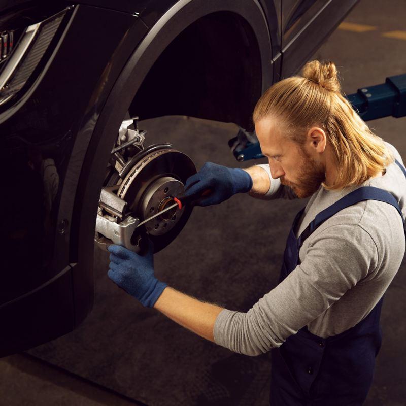 Ein VW Servicemitarbeiter prüft den Verschleiß an einer Bremse – Wartung und Verschleiß