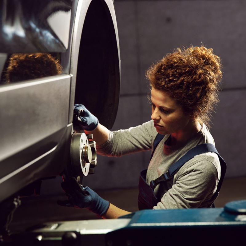Mechanikerin arbeitet an einem Volkswagen