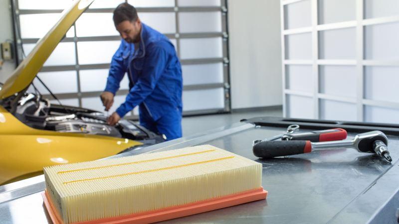 VW Servicemitarbeiter arbeitet an einem Volkswagen – Wartungspakete