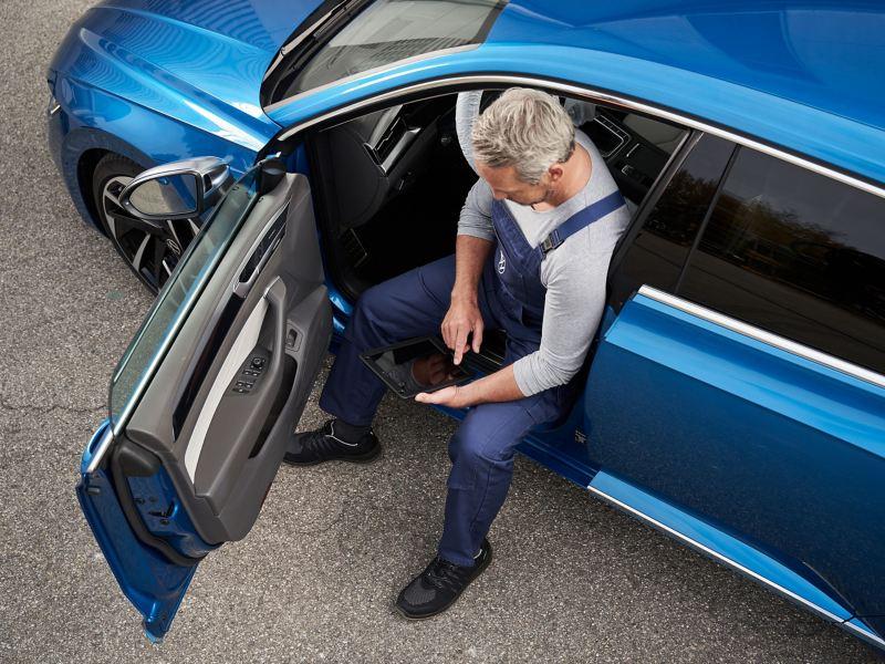 Eine VW Servicemitarbeiterin arbeitet an einem Volkswagen – VW Wartungsverträge